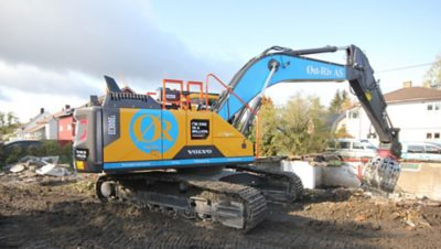 Blue and yellow Volvo excavator at a construction site in Oslo, Norway