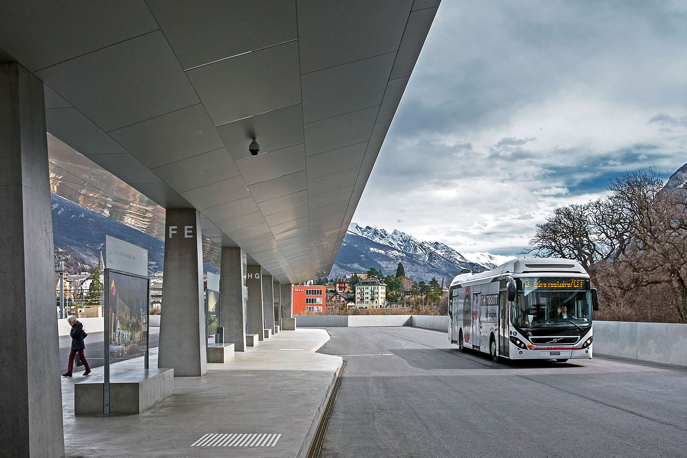 A Volvo full hybrid bus in Sierre's modern bus station with mountains in the background