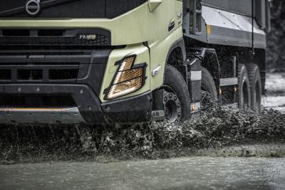 A Volvo FMX drives through the mud