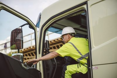 A driver wearing a hard hat sits in his cab with the door open