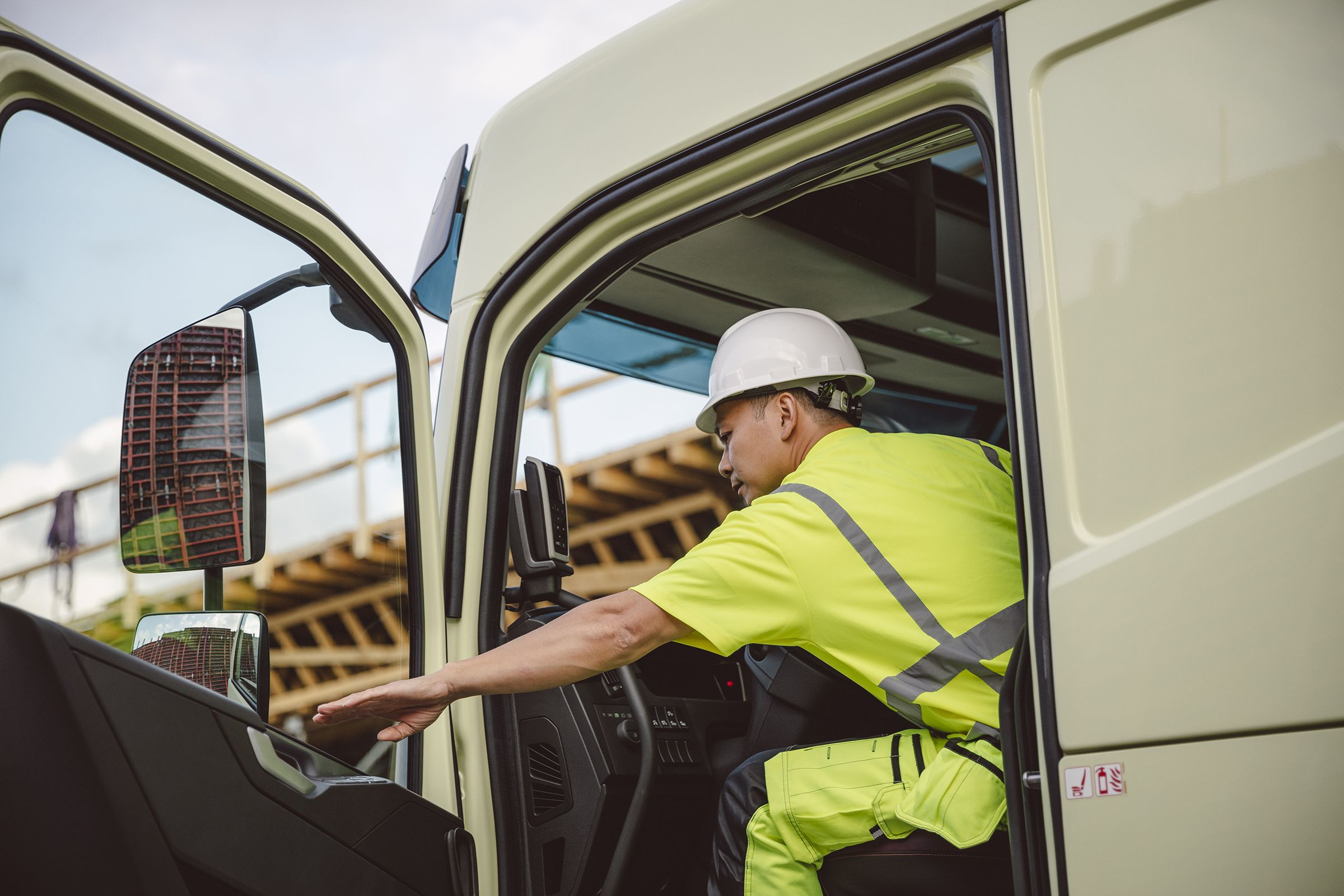 คนขับที่สวมหมวกนิรภัยนั่งอยู่ในรถโดยเปิดประตู