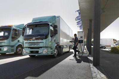 Un conductor carga su camión eléctrico