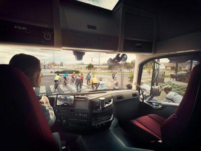 Водитель на дороге позади группы велосипедистов