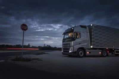 Un camión estacionado de noche con las luces interiores encendidas.