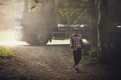 En lastebil parkert bak en mann som går gjennom en skog