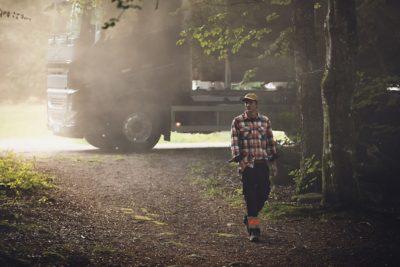 A truck parked behind a man walking through a forest