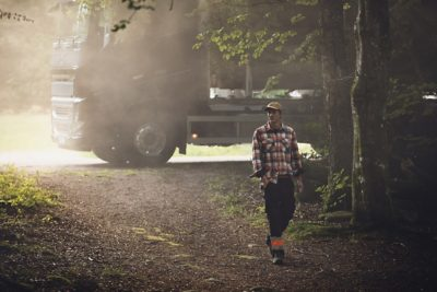 숲을 걷는 남자 뒤에 주차된 트럭