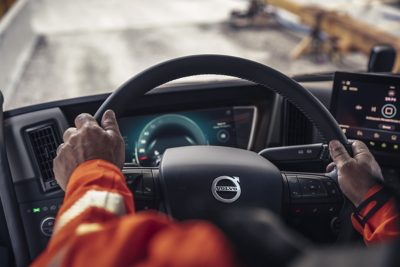 Closeup of two hands on a steering wheel