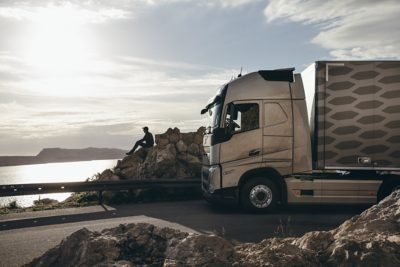 A truck parked behind a driver who is sitting on rocks and looking out over the water
