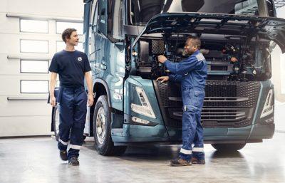 Two technicians speak in front of truck in the workshop