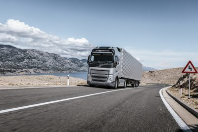 A truck drives along the coast with mountains in the distance
