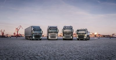 Four trucks stand in a row in front of a crane