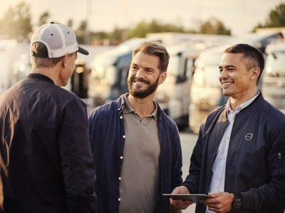 Tres hombres hablan frente a una flota de camiones