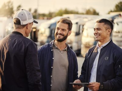 Drie mannen staan te praten voor een wagenpark van trucks