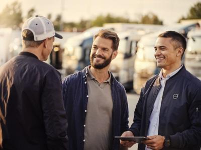 Três homens falam em frente de uma frota de camiões