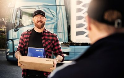 A driver holds a blue Genuine Volvo Parts box as he talks to someone