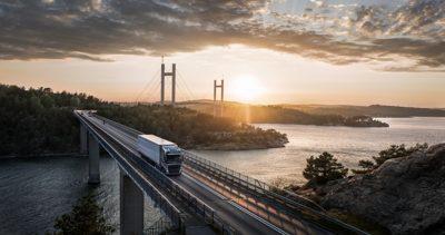 Nákladné vozidlo Volvo jazdí po moste nad vodou, keď za ním zapadá slnko