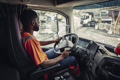 Pro krovimo rampoje esantį sunkvežimį praeina žmogus su rankiniu sunkvežimiu