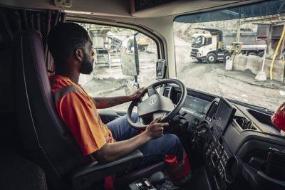 ชายคนหนึ่งขณะลากรถเข็นขนสินค้าผ่านรถบรรทุกภายในท่าขนถ่าย