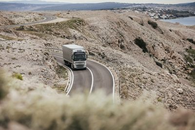 A truck drives over dusty mountains along the coast
