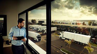 Volvo FMX productivity man looking at trucks