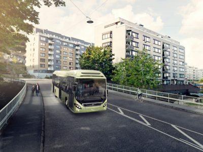 A full hybird bus on the street in an urban area