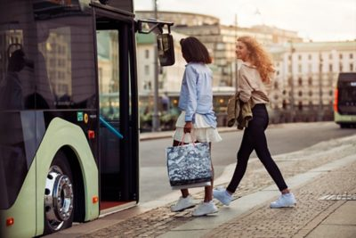 Two women about to board a full hybrid bus in a city location