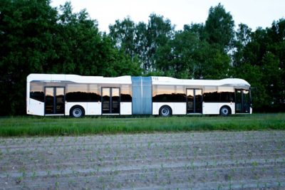 An articulated full hybrid bus drives alongside crops in a field