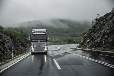 A truck drives around a bend through the rain