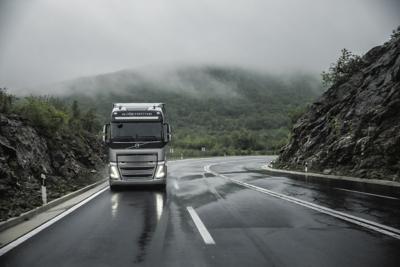 Un camión traza una curva bajo la lluvia