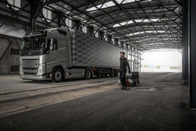 Vīrietis ar rokas ratiņiem iet gar kravas automašīnu uz rampas