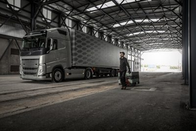 A man with a handtruck walks by a truck inside a loading dock