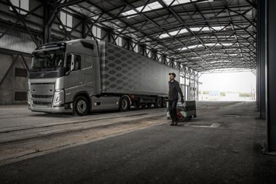 一人推著手推車路過一輛卸貨平台內的貨車