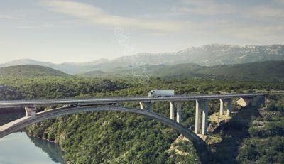 En tilkoblet Volvo-lastebil kjører over en bro på et avsidesliggende sted