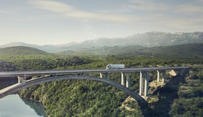 Un autocamion Volvo conectat rulează peste un pod într-o regiune îndepărtată