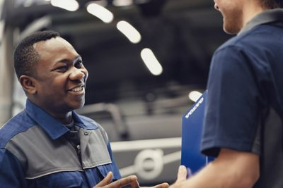 A smiling Volvo service technician speaks to a colleague