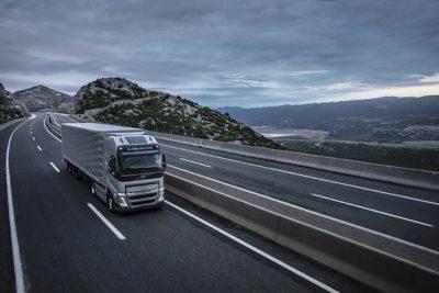 Un camión pasa por un puente con montañas al fondo