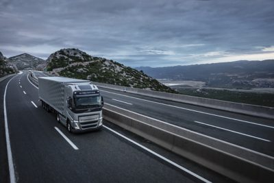 A truck drives over a bridge with mountains in the background