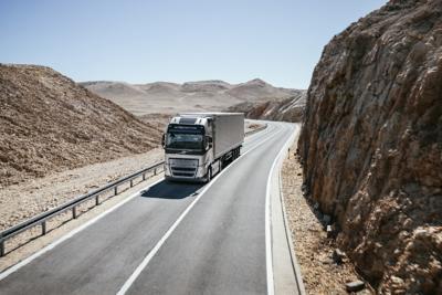 A truck drives through a mountainous desert landscape