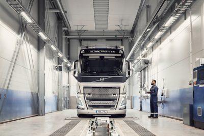 En Volvo-servicemekaniker ser på en lastbil og holder en computer