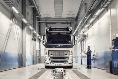 A Volvo service technician holding a computer looks at a truck