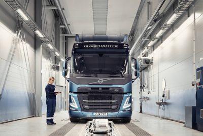 Uma técnica de assistência Volvo segura num computador ao lado de um camião