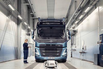 A Volvo service technician holds a computer as she stands next to a truck