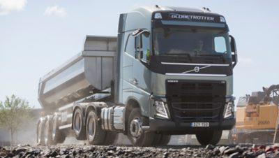 Volvo FH con remolque y levantamiento del eje tándem en caminos de grava