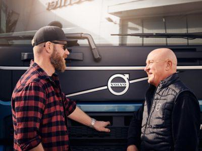 Two men speak in front of a Volvo truck