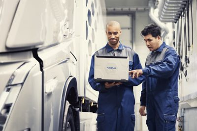 Two Volvo service technicians look at a laptop while standing next to a truck