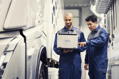 Twee Volvo-servicemonteurs kijken op een laptop terwijl ze naast een truck staan