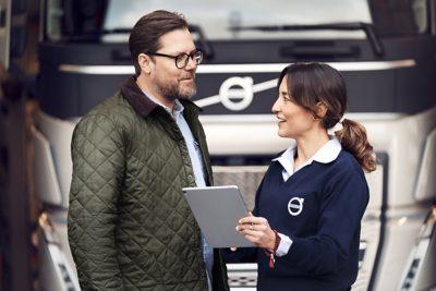 Een Volvo-vertegenwoordiger spreekt met een klant terwijl hij een tablet vasthoudt