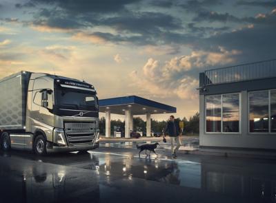 Een chauffeur loopt met zijn hond voor een Volvo-truck die bij een tankstation staat geparkeerd