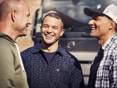 A close up of three men smiling in front of a Volvo truck